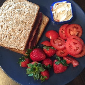 Turkey bacon on whole grain bread with strawberries and tomatoes and hummus.
